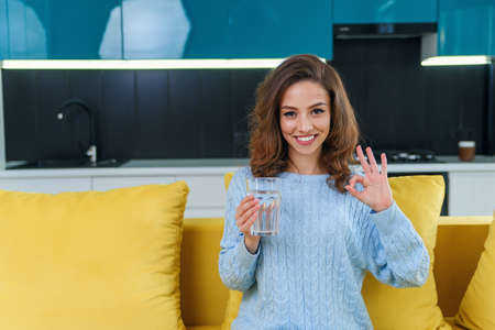 Beautiful woman holds a glass of pure water and showing ok sign by hand at home. Lifestyle concept and healthy concept. Stockfoto - 132629493
