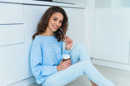 Pretty exuberant young woman in casual stylish clothes enjoying tasty chocolate cream and looking at camera with cute smile in the cuisine interior. Stockfoto