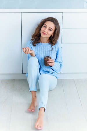 Pretty exuberant young woman in modern stylish clothes enjoying tasty chocolate and looking at camera with cute smile in the cuisine interier