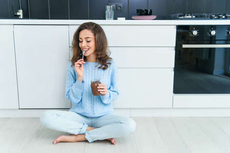 Lovely happy exuberant woman with wavy brown hair eating delicious chocolate cream and closing her eyes from pleasure.