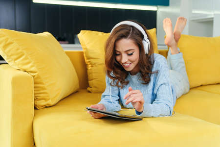 Exuberant happy woman uses tablet pc while laying on the comfortable yellow sofa and listens to music with earphones. Stockfoto