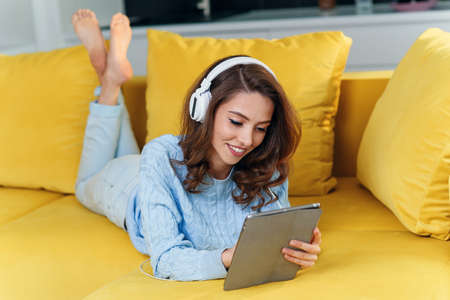 Exuberant happy woman uses tablet pc while laying on the comfortable yellow sofa and listens to music with earphones. Stockfoto - 132438587