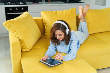 Exuberant happy woman uses tablet pc while laying on the comfortable yellow sofa and listens to music with earphones. Stockfoto - 132438561