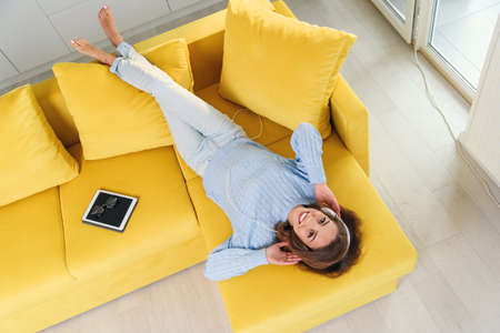 Satisfied cheerful girl lying on the comfortable yellow couch and listens to the music on her white earphones. Top view. Stockfoto - 132347377