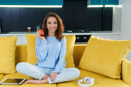 Beautiful female vegetarian in casual clothes holds fresh red apple while sitting on comfortable yellow sofa in the stylish modern kitchen.