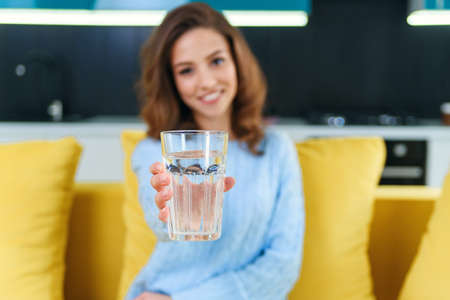 Beautiful young happy woman with glass of crystal clear water sitting on soft yellow couch. Stockfoto