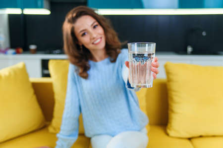 Adorable cheerful wavy-haired woman looking at camera with a glass of fresh water on the kitchen background Stockfoto