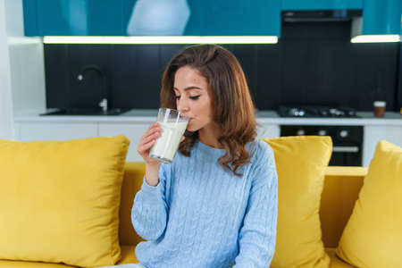 Happy businesswoman drinking a cup of coffee in her sofa