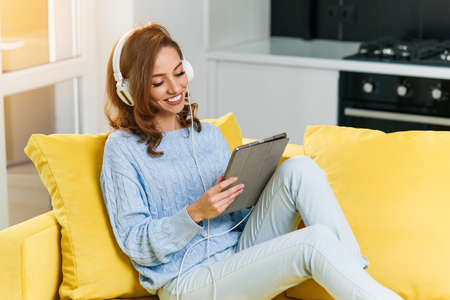 Exuberant 30-aged girl with wavy brown hair wearing white earphones listens music and uses laptop or tablet, resting on the yellow couch at cozy home.