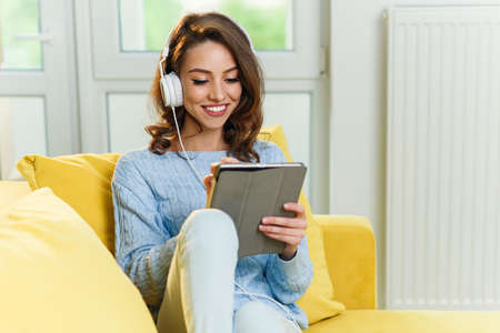 Young beautiful girl sitting on modern yellow couch and listens to music and uses tablet at the home. Stockfoto