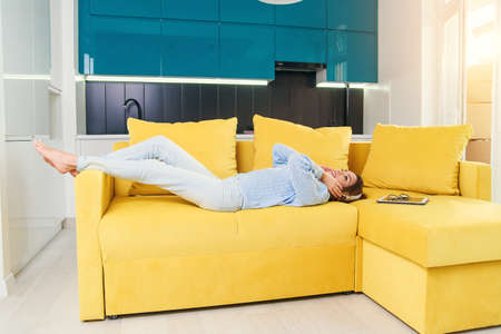 Pretty teenage girl in headphones listening to music while lying on her back on sofa at modern stylish kitchen. Young happy woman relaxing at cozy home.