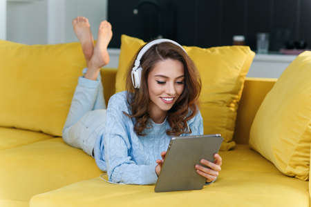 Exuberant girl uses tablet pc while laying on the comfortable yellow sofa and enjoying nice melodies with earphones.