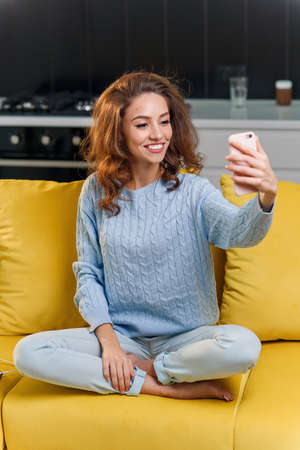 Beautiful girl with cute smile makes selfie on the cuisine background. Cheerful girl speaks online with her boyfriend by smartphone.