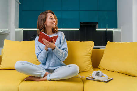 Attractive female writer in glasses writes her personal records into notebook while sitting in comfortable yellow couch in stylish modern kitchen. Stockfoto - 132604352