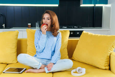 Attractive woman in casual clothes eating fresh juicy red apple while sitting on comfortable yellow couch in the contemporary kitchen.