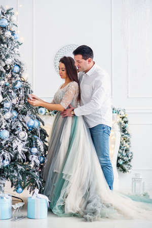 Couple in love stand together near Christmas tree and look at each other. 版權商用圖片