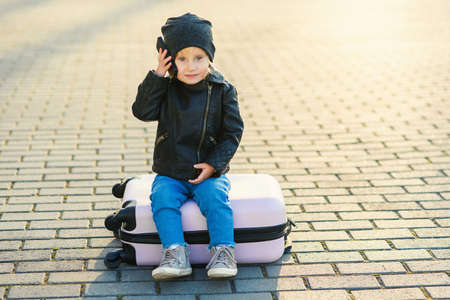 Beautiful little traveler girl sits on pink suitcase and talking on cell phone near airport on the background of sunset. Stockfoto
