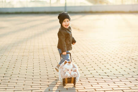 Little smiling traveler girl pulls funny fluffy suitcase with rabbit to the airport.