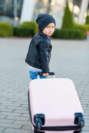 Cute little traveler girl pulls pink suitcase towards the airport. Foto de archivo - 133511050