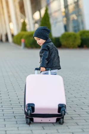 Cute little traveler girl pulls pink suitcase towards the airport. Foto de archivo - 133511053