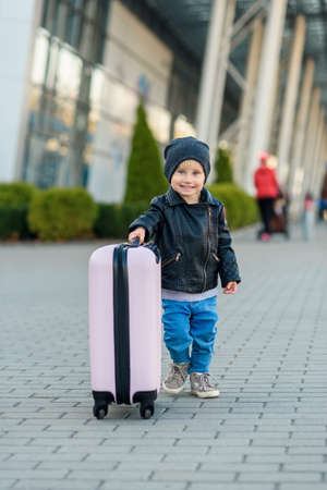 Beautiful happy girl travels with stylish suitcase. Little child traveler goes to the trip from airport. Foto de archivo - 133511055