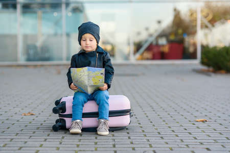 Funny little girl sits on pink suitcase with map in hands near the airport.