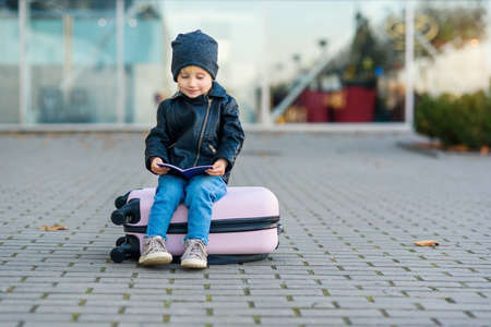 Funny little girl sits on pink suitcase with her passport in hands on the background of airport. Foto de archivo - 133510966