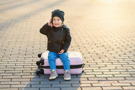 Little traveler girl sits on pink suitcase and talking on smartphone near airport against sunset.