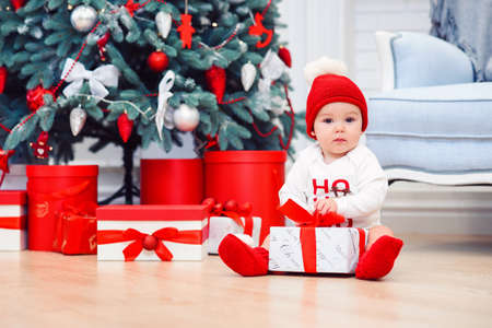 baby unpack gift boxes with christmas decoration, dressed as Santa, boke lights on dark background, winter holiday concept Stockfoto