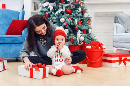 Charming toddler with her mother unpacking holidays gift.
