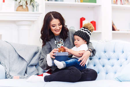 Cute little baby resting on her mothers knees which sitting on the comfortable blue sofa in the festive decorated christmas room. Stockfoto