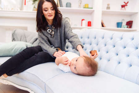 Cute toddler lies on the blue couch and happy young mommy kneading his legs and makes him happy.