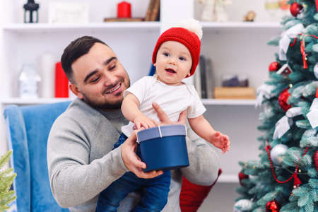 Young father sits in comfortable chair holding amusing toddler and gives gift box to him in the wonderfully decorated room to celebrate christmas.