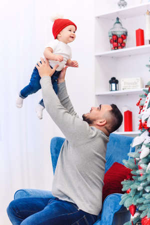 Handsome dad throwing up his amusing infant boy in the air near festive decorated christmas tree.