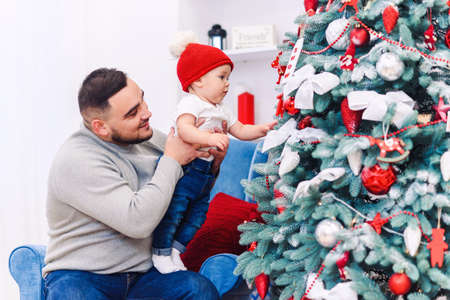 Man and cute baby are ready to celebrate new year. Happy father plays with his infant son near Christmas Tree in Christmas evening.