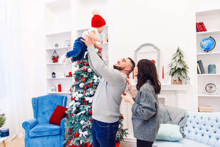 Attractive mommy stands near handsome gorgeous dad which throwing up their adorable little son in the air near festive decorated christmas tree. Stockfoto