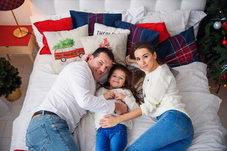 Merry Christmas and Happy New Year Happy family lying in bed near beautiful Christmas tree.