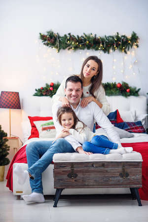 Parents with their little kid sitting near christmas tree Stockfoto
