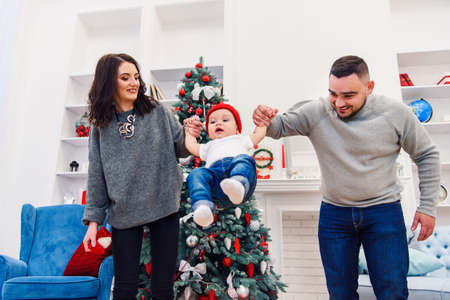 Attractive picture of beautiful family which spending their time with fun with incredible nice infant near wonderfully decorated christmas tree