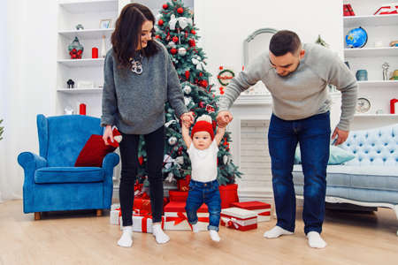 Happy young mother and father holding their sweet infant by hands and raising them high in the decorated room to celebrate christmas
