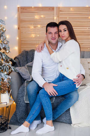 Attractive cheerful man and woman sitting near christmas tree and hugging each other. New Years eve.