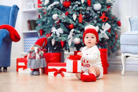 Charming toddler boy holds christmas gift box. Concept of Christmas holidays.