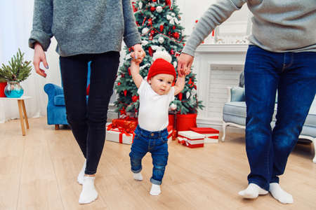 Mom and dad holding their cute baby and teaching him how to walk in the middle of the christmas decorated room.