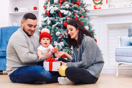 Young family gives the first Christmas gift box to their newborn child. Toddler boy receives his first christmas gift. Stockfoto