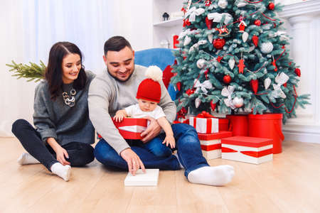 Young parents help to unpacking the first Christmas gift to their newborn child. Toddler boy receives his first christmas gift. Stockfoto