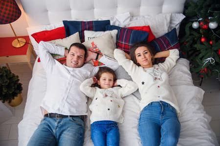 Merry Christmas and Happy New Year Happy family lying in bed near beautiful Christmas tree. Foto de archivo - 133510974