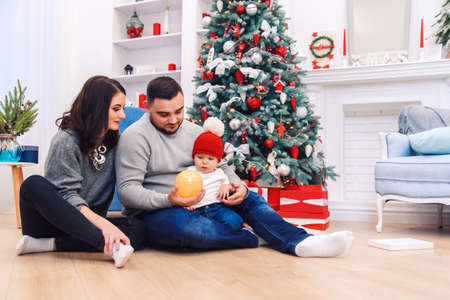 Young parents help to unpacking the first Christmas gift to their newborn child. Toddler boy receives his first christmas gift. Foto de archivo - 133510976
