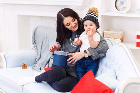 Cute baby having fun with her mother on the comfortable blue sofa in the festive decorated christmas room. Happy winter holidays concept. Foto de archivo - 133510977