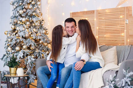 Young mom, father, and their little daughter lovely sitting near Christmas tree on sofa. Stockfoto