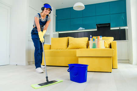 Beautiful young female professional cleaner in special uniform with headphones washing the floor with mop and listens to music at apartment.